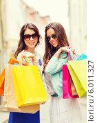 Купить «Шопинг в городе. Две привлекательные девушки с пакетами на улице», фото № 6011327, снято 29 июня 2013 г. (c) Syda Productions / Фотобанк Лори