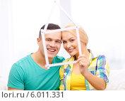 Новый дом, сделанный из складной линейки, на фоне счастливой молодой пары. Стоковое фото, фотограф Syda Productions / Фотобанк Лори