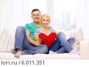 Купить «Счастливая молодая пара с большим сердцем в руках сидит на диване дома», фото № 6011351, снято 16 февраля 2014 г. (c) Syda Productions / Фотобанк Лори