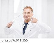 Купить «Врач-стоматолог объясняет, как правильно чистить зубы», фото № 6011355, снято 6 июля 2013 г. (c) Syda Productions / Фотобанк Лори