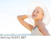 Купить «Элегантная привлекательная девушка весело смеется, придерживая рукой белую шляпу с широкими полями», фото № 6011367, снято 19 июня 2013 г. (c) Syda Productions / Фотобанк Лори