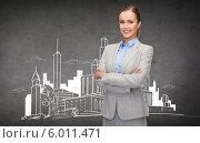 Купить «Уверенная бизнес-леди стоит, скрестив руки, на фоне серой стены с рисунком современного города», фото № 6011471, снято 16 января 2019 г. (c) Syda Productions / Фотобанк Лори