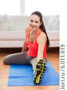 Фитнес дома. Привлекательная девушка выполняет упражнения, сидя на полу на коврике в квартире. Стоковое фото, фотограф Syda Productions / Фотобанк Лори