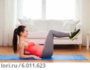 Привлекательная девушка выполняет фитнес-упражнения на специальном коврике в своей квартире. Стоковое фото, фотограф Syda Productions / Фотобанк Лори