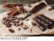 Темный шоколад, палочки корицы, сахар-рафинад, нож и какао-бобы на оберточной бумаге на деревянном столе. Стоковое фото, фотограф Natasha Breen / Фотобанк Лори
