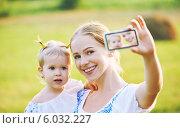 Мама с маленькой дочерью на руках фотографируется на мобильный телефон. Стоковое фото, фотограф Евгений Атаманенко / Фотобанк Лори