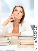 Купить «Привлекательная задумчивая бизнесвумен сидит за столом, облокотившись на стопки книг», фото № 6033027, снято 18 июля 2013 г. (c) Syda Productions / Фотобанк Лори