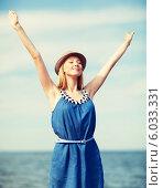 Красивая стройная девушка в синем платье и шляпе стоит на морском берегу, подняв руки вверх. Стоковое фото, фотограф Syda Productions / Фотобанк Лори