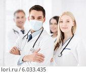 Купить «Врач в медицинской маске стоит вместе со своими коллегами», фото № 6033435, снято 18 мая 2013 г. (c) Syda Productions / Фотобанк Лори
