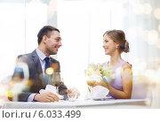 Мужчина дарит цветы девушке во время встречи в ресторане. Стоковое фото, фотограф Syda Productions / Фотобанк Лори