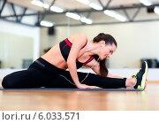 Купить «Девушка выполняет наклоны, сидя на полу в спортивном зале», фото № 6033571, снято 28 сентября 2013 г. (c) Syda Productions / Фотобанк Лори