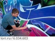 Купить «Молодой художник рисует пульверизатором граффити на фестивале Extreme Fest на Нижней набережной города Иркутска, Россия», фото № 6034603, снято 24 мая 2014 г. (c) Николай Винокуров / Фотобанк Лори