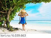 Девушка в синем платье качается на качелях на тропическом пляже около моря в солнечный день. Стоковое фото, фотограф Николай Охитин / Фотобанк Лори