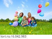 Купить «Счастливая многодетная семья сидит на траве с воздушными шарами», фото № 6042983, снято 17 мая 2014 г. (c) Сергей Новиков / Фотобанк Лори