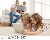 Купить «smiling sister with tablet pc and parents on back», фото № 6044367, снято 1 марта 2014 г. (c) Syda Productions / Фотобанк Лори