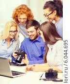 Купить «smiling team with laptop and photocamera in office», фото № 6044695, снято 1 февраля 2014 г. (c) Syda Productions / Фотобанк Лори