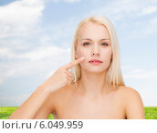 calm young woman pointing at her cheek. Стоковое фото, фотограф Syda Productions / Фотобанк Лори