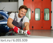 Купить «Young serviceman performing grinding with machine on a car bonnet in a workshop», фото № 6055939, снято 12 июня 2014 г. (c) Andrejs Pidjass / Фотобанк Лори
