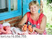 Бабушка с вязаными детскими пинетками в руках. Стоковое фото, фотограф Типляшина Евгения / Фотобанк Лори