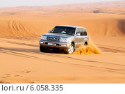 Купить «Автомобиль едет по пустыне. Поездка на внедорожнике является главной экскурсией в Дубае, ОАЭ», фото № 6058335, снято 22 мая 2010 г. (c) Chere / Фотобанк Лори