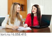 Купить «Smiling women looking financial documents», фото № 6058415, снято 21 марта 2014 г. (c) Яков Филимонов / Фотобанк Лори