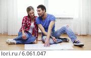 Купить «Smiling couple discussin blueprint at home», видеоролик № 6061047, снято 31 января 2014 г. (c) Syda Productions / Фотобанк Лори