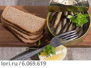 Купить «Шпроты в банке и ржаной хлеб на деревянной доске», фото № 6069619, снято 29 июня 2014 г. (c) Леонид Штандель / Фотобанк Лори