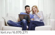 Купить «Smiling couple with laptop computer at home», видеоролик № 6070271, снято 16 февраля 2014 г. (c) Syda Productions / Фотобанк Лори