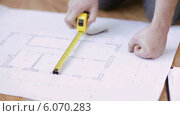 Купить «Close up of male hands measuring blueprint», видеоролик № 6070283, снято 10 февраля 2014 г. (c) Syda Productions / Фотобанк Лори