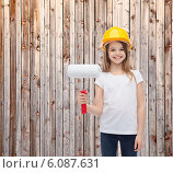 Купить «smiling little girl in helmet with paint roller», фото № 6087631, снято 9 апреля 2014 г. (c) Syda Productions / Фотобанк Лори
