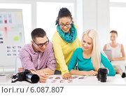 Купить «smiling team with printed photos working in office», фото № 6087807, снято 17 мая 2014 г. (c) Syda Productions / Фотобанк Лори