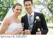 Newly wed couple holding champagne glasses. Стоковое фото, агентство Wavebreak Media / Фотобанк Лори