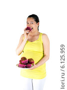 Купить «Беременная женщина ест сладкие кексы. Pregnant woman eating muffins», фото № 6125959, снято 8 июля 2014 г. (c) Сергей Левыкин / Фотобанк Лори