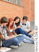 Купить «Students friends sitting on ground outside campus», фото № 6134367, снято 19 июня 2014 г. (c) CandyBox Images / Фотобанк Лори