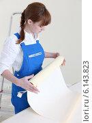 Купить «Woman unrolling wallpaper», фото № 6143823, снято 12 января 2010 г. (c) Phovoir Images / Фотобанк Лори