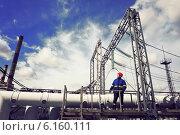 Электромонтёр осматривает электрооборудование электрической подстанции. Стоковое фото, фотограф yeti / Фотобанк Лори