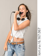 Купить «Singing teenage girl with microphone closed eyes», фото № 6167067, снято 1 июля 2014 г. (c) CandyBox Images / Фотобанк Лори