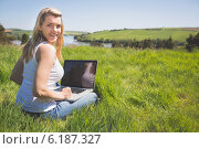 Купить «Pretty blonde sitting on grass using her laptop smiling at camera», фото № 6187327, снято 28 мая 2014 г. (c) Wavebreak Media / Фотобанк Лори