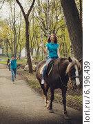Парень догоняет девушку, сидящую на лошади, в весеннем парке. Стоковое фото, фотограф Юлия Ротанина / Фотобанк Лори