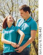 Молодой человек и девушка в одинаковых футболках смотрят друг на друга в парке весной. Стоковое фото, фотограф Юлия Ротанина / Фотобанк Лори