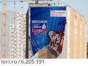 Монтажники вешают большой баннер на стену здания, Челябинск (2014 год). Редакционное фото, фотограф Михаил Мандрыгин / Фотобанк Лори