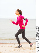 smiling young woman running outdoors. Стоковое фото, фотограф Syda Productions / Фотобанк Лори