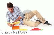 Купить «Handsome young student studying on floor», видеоролик № 6217487, снято 29 марта 2020 г. (c) Wavebreak Media / Фотобанк Лори