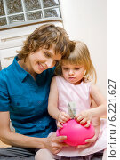 Mother and daughter putting money into piggy bank. Стоковое фото, агентство BE&W Photo / Фотобанк Лори