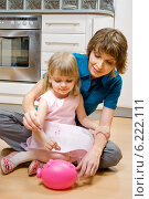 Mother and daughter putting coins into piggy bank. Стоковое фото, агентство BE&W Photo / Фотобанк Лори