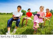 Купить «Группа детей сидит с планшетами для бумаг на природе», фото № 6222655, снято 8 июня 2014 г. (c) Сергей Новиков / Фотобанк Лори