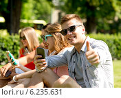 Купить «smiling man with smartphone showing thumbs up», фото № 6235631, снято 20 июля 2014 г. (c) Syda Productions / Фотобанк Лори