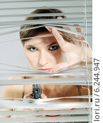 Woman's portrait taking a shoot out of the blinds. Стоковое фото, агентство BE&W Photo / Фотобанк Лори