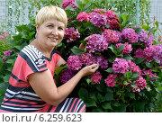 Радостная женщина средних лет рядом с цветущей гортензией в саду. Стоковое фото, фотограф Ирина Борсученко / Фотобанк Лори