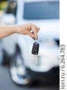 Купить «Женская рука держит ключ зажигания на фоне размытого автомобиля», фото № 6264783, снято 20 июля 2014 г. (c) Кекяляйнен Андрей / Фотобанк Лори